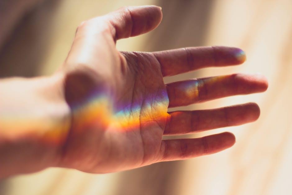 虹色の光を受け止めている手のひら