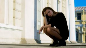 道端で頭を抱え疲れた表情の女性