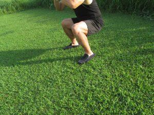 芝生でスクワットをしている男性
