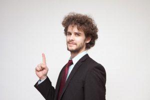 人差し指を立てているアフロヘアの外国人男性