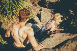 topless-man-behind-woman-walking-on-gray-rock-formation-during-daytime