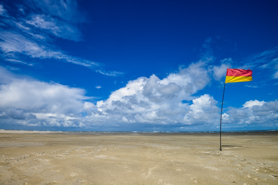砂漠に立っている赤と黄色の旗