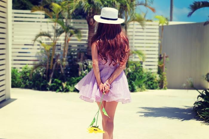 ひまわりを後ろ手に持ったワンピースを着た女の子
