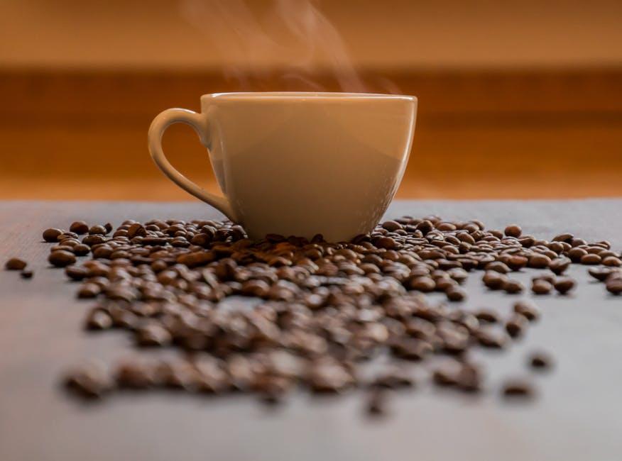 ちらばったコーヒー豆とコーヒーカップ