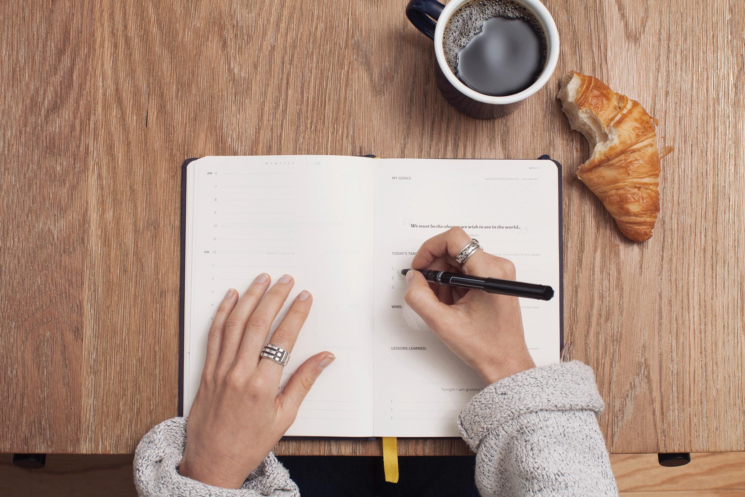クロワッサンとコーヒーを傍にメモをする女性の手元