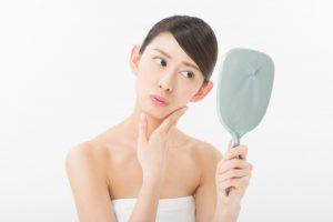 鏡を見ながら首をかしげる女性