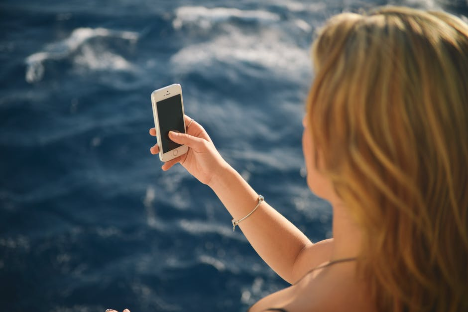 海の写真を撮る女性