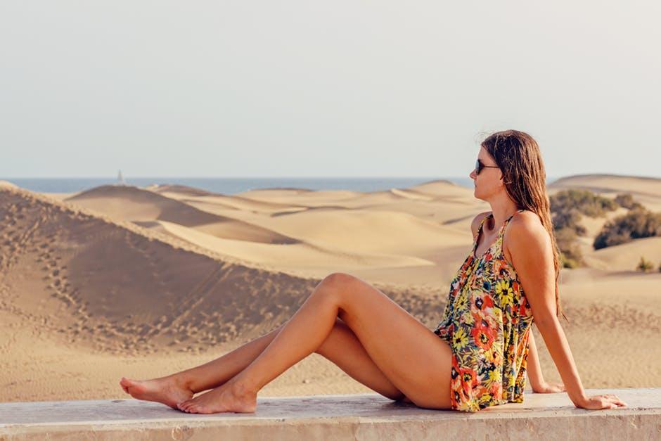 砂漠と海を背景に座っている女性